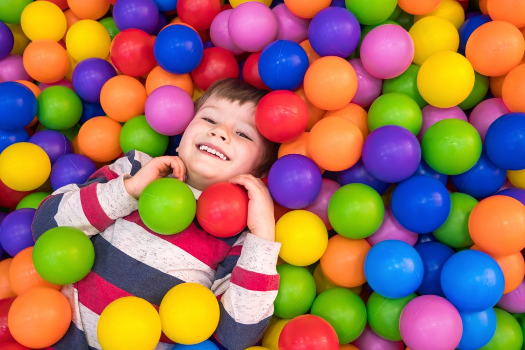 Boy playing in a ball pit.
